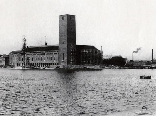 Stadshuset har blivit själva symbolen för Stockholm fastän de tre kronorna på tornets spets egentligen är staten Sveriges riksvapen. Ännu var nyfikenheten stor 1919 när bilden togs om hur tornet skulle komma att se ut. Bygget hade pågått i över ett decennium redan. Observera fabriksskorstenarna! Staden var fortfarande en industristad. Det rådde badförbud i Riddarfjärden, vattnet var förgiftat av industriföroreningar.